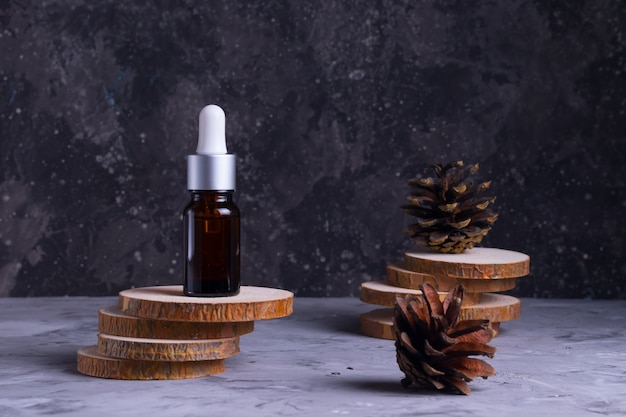Befeuchtendes serum mit kollagen und mucin einer schnecke für die gesichtshaut gegen falten und akne in einer glasflasche auf holzstützen mit zapfen auf grauem hintergrund