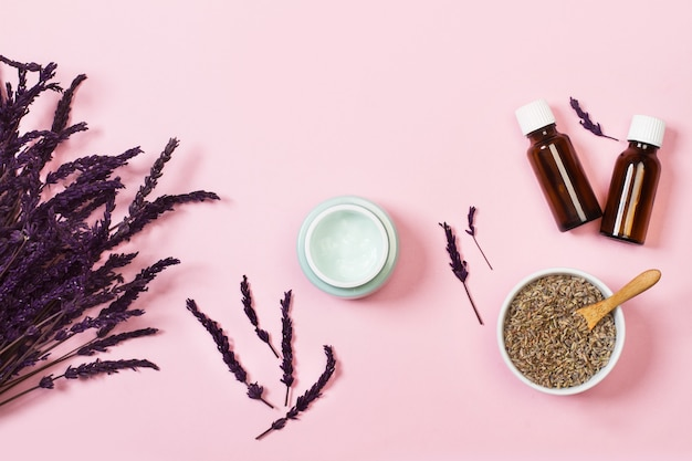Befeuchtete creme auf einem rosa hintergrund mit lavendelblumen in einer draufsicht