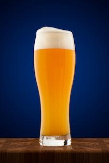Befeuchtete volle tasse kaltes bier auf einem holztisch