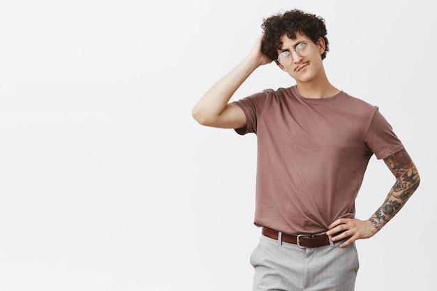 Befragter verwirrter, gut aussehender hipset-typ mit dunklem lockigem haar und schnurrbart, der den kopf kratzt und besorgt und vergesslich aussieht