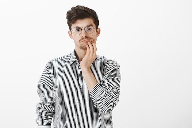 Befragter zweifelhafter attraktiver bärtiger kerl mit schnurrbart in runder brille, hand am kinn haltend und nach unten schauend, während er während des gesprächs nachdenkt oder abstand hält, weg von der diskussion