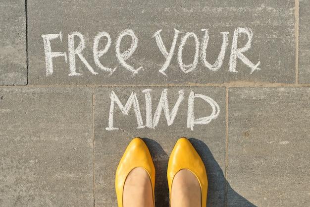 Befreie deinen gedanken-text auf grauem bürgersteig mit frauenbeinen