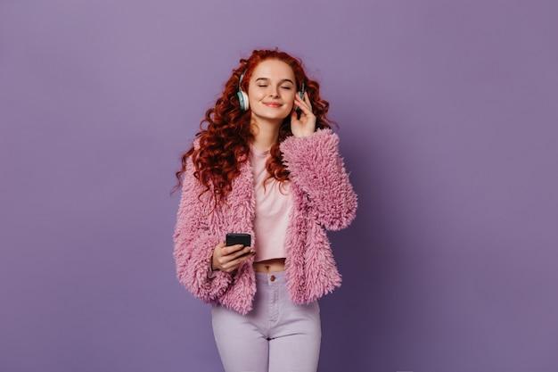 Befriedetes mädchen im stilvollen rosa und weißen outfit, das musik in blauen kopfhörern genießt. rothaarige frau, die mit smartphone auf fliederraum aufwirft.