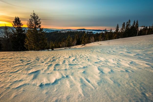 Befriedungslandschaft im gebirgstal mit fichtenwald und schneeverwehungen vor dem hintergrund ohne sonnenuntergang und blauen himmel mit wolken