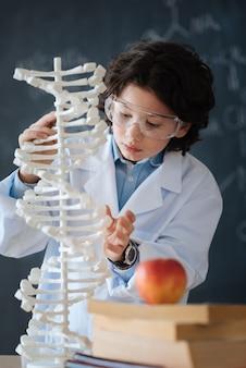 Begabter schüler, der die wissenschaft erforscht. fleißiges, geschicktes, fleißiges kind, das in der schule vor der tafel steht, während es wissenschaft studiert und an dem projekt arbeitet