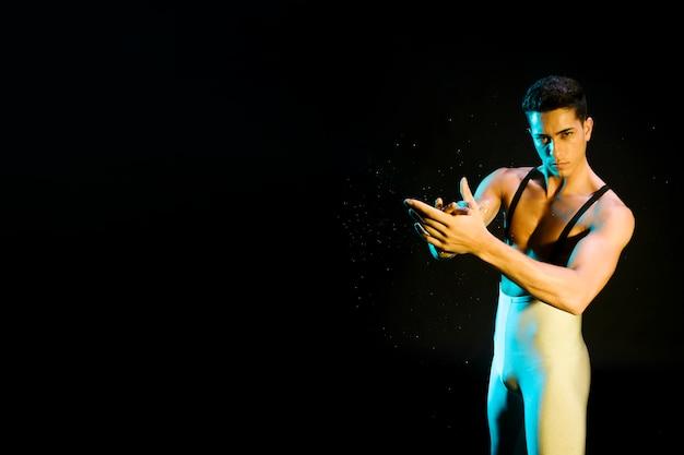 Begabter zeitgenössischer tänzer, der im scheinwerferlicht durchführt