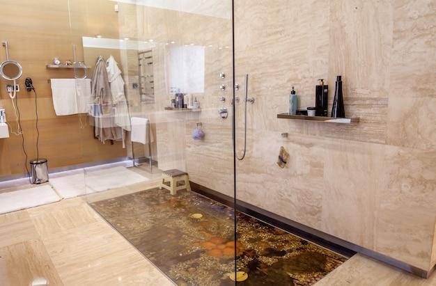 Begehbare dusche mit chromarmaturen und marine-dekor auf dem boden im badezimmer