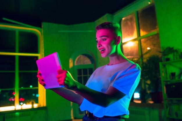 Begeistert. filmporträt der stilvollen frau im neonbeleuchteten innenraum. getönt wie kinoeffekte, leuchtende neonfarben. kaukasisches modell mit tablette in bunten lichtern drinnen. jugendkultur.