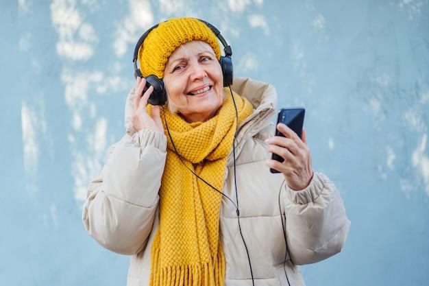 Begeisterte ältere frau, die musik hört und smartphone benutzt