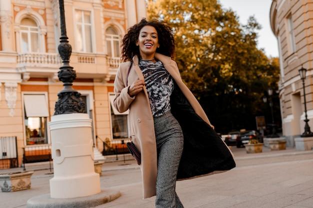 Begeisterte afrikanerin im eleganten freizeitoutfit, das läuft und spaß hat.