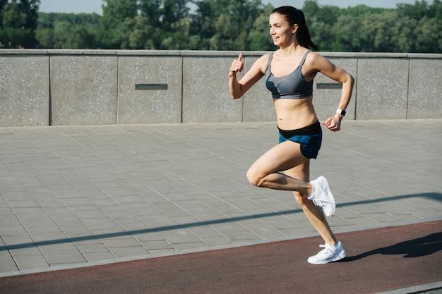 Begeisterte athletische frau, die schnell draußen auf der strecke neben dem bürgersteig läuft. an einem sonnigen tag unter strahlend blauem himmel. sie trägt ein graues top und mini-shorts.