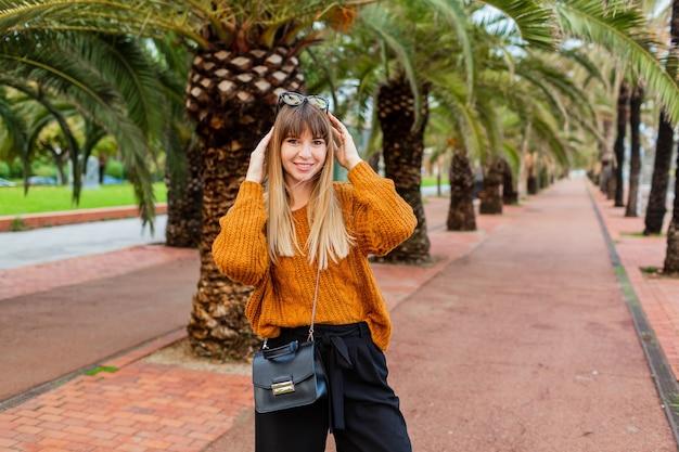Begeisterte blonde frau in stylischer sonnenbrille posiert über der strandpromenade von barcelona