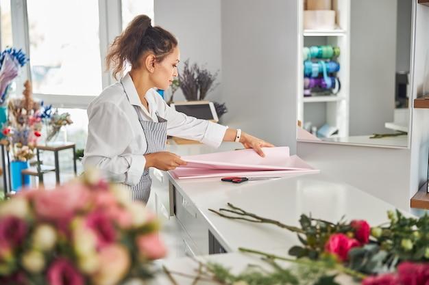 Begeisterte brünette frau, die geschenkpapier auf dem tisch berührt
