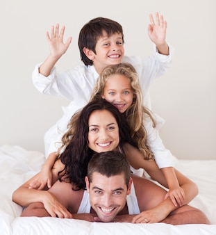Begeisterte familie, die auf ihrem bett liegt
