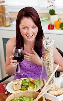 Begeisterte frau, die ihre mahlzeit zu hause hält ein glas wein isst