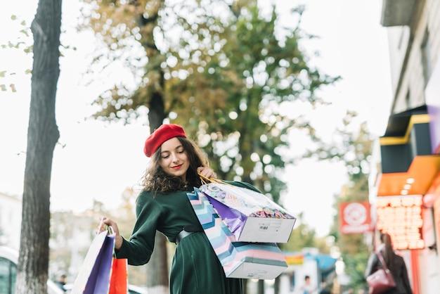 Begeisterte frau mit einkaufstaschen auf straße