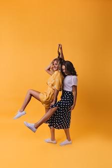Begeisterte freundinnen in trendigen gummischuhen, die lustig auf gelb tanzen. wunderbare schwestern, die freizeit genießen.