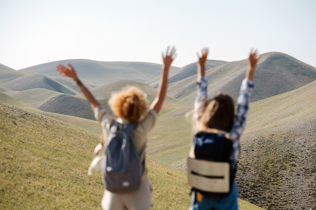 Begeisterte freundinnen springen auf der stelle inmitten einer wunderschönen hügellandschaft. hände in die luft werfen. hinterrücks.
