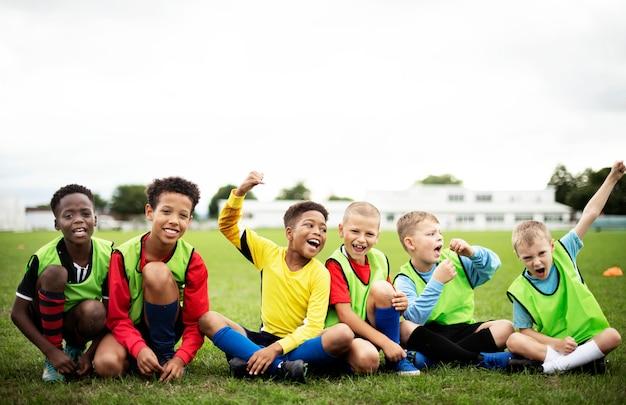 Begeisterte fußballspieler, die auf dem feld sitzen
