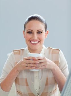 Begeisterte geschäftsfrau, die einen kaffee trinkt