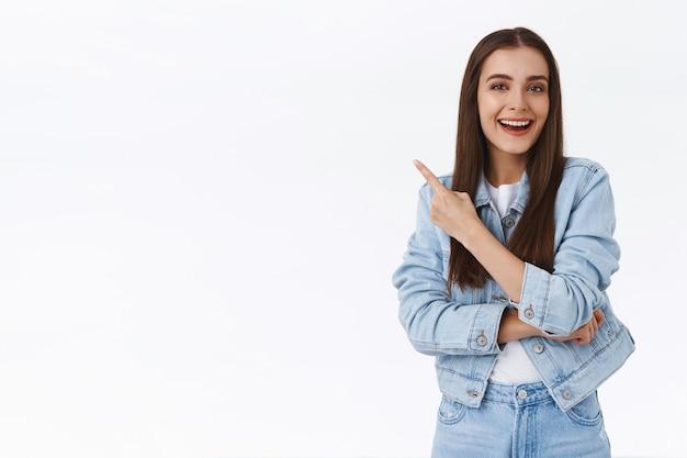 Begeisterte junge attraktive kaukasische frau, die über tolle werbung lacht, die obere linke ecke zeigt beeindruckt und erfreut, lächelnde kamera als diskussion über coole promo, weißer hintergrund
