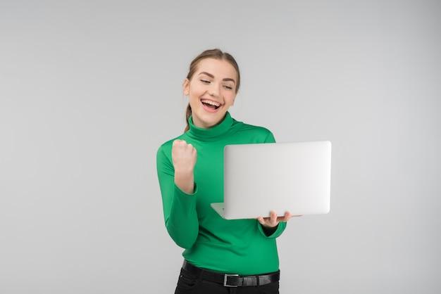 Begeisterte junge frau, die laptop mit siegreichem ausdruck betrachtet. hält gerät und faust hoch. - konzeptbild