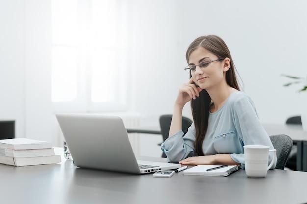 Begeisterte junge frau, die laptopschirm im büro betrachtet.