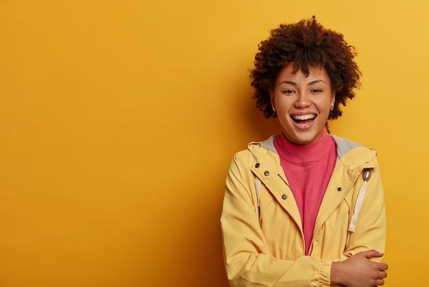 Begeisterte lustige frau mit afro-frisur, lacht laut, stellt sich eine lustige situation vor, hält die hände über der brust gekreuzt, lässig gekleidet, steht an der gelben wand