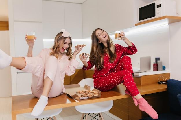 Begeisterte mädchen in socken und pyjamas trinken gemeinsam orangensaft. lachende weiße damen, die spaß beim frühstück haben.