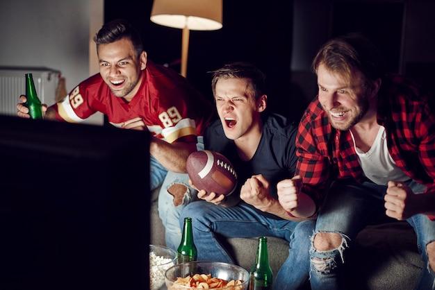 Begeisterte männer, die ihr team unterstützen