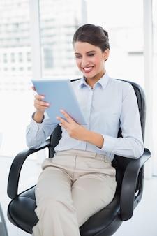 Begeisterte noble braune behaarte geschäftsfrau, die einen tabletten-pc verwendet