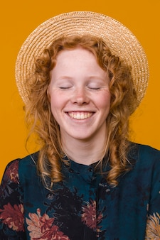 Begeisterte rothaarigefrau im hut im studio