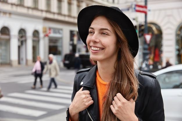 Begeisterte touristin hat einen fröhlichen ausdruck, ein zahniges lächeln mit weißen zähnen, ausflug in die stadt