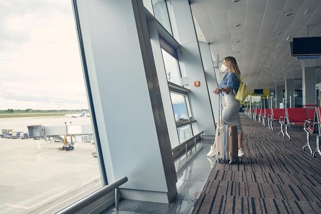 Begeisterte weibliche person, die eine maske trägt, während sie am flughafen ist und alleine reisen wird