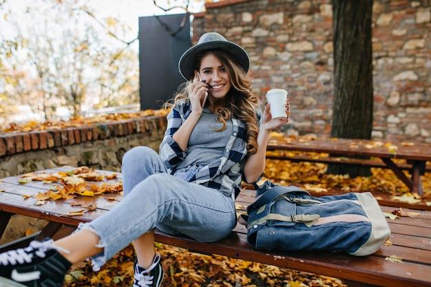 Begeisterte weiße dame mit langer frisur, die auf picknicktisch mit blauem rucksack sitzt