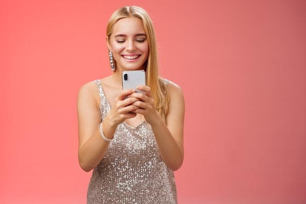 Begeisterte zarte glamour-blondine in silbernem, stylischem, glitzernden kleid mit brillanten ohrringen, die ein smartphone halten und einen fotofreund aufnehmen, der den moment feiern, den nachtclub, den roten hintergrund lächelt.