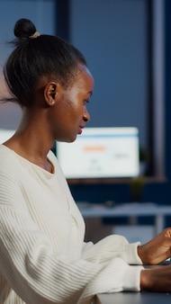 Begeisterter afrikanischer ingenieur, der cad-software analysiert, um ein 3d-konzept von containerüberstunden in einem start-up-unternehmen für einen prototyp zu entwerfen. überarbeitete frau, die im büro mit technologie studiert