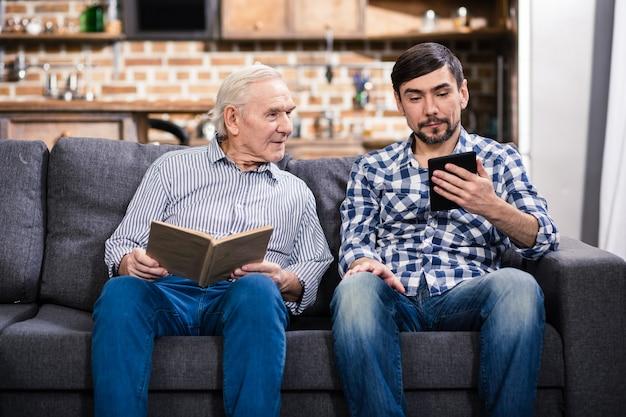 Begeisterter alter mann, der ein buch liest, während sein sohn eine tablette benutzt
