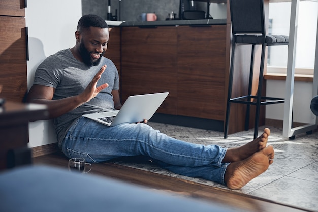 Begeisterter dunkelhäutiger mann, der ein lächeln auf seinem gesicht behält, während er auf den bildschirm seines laptops schaut