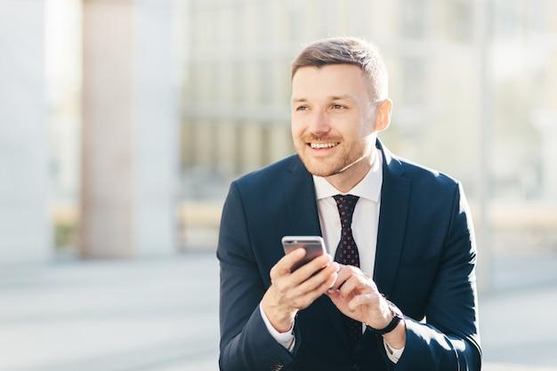 Begeisterter durchdachter eleganter männlicher marketing-händler im formalen schwarzen anzug, benutzt modernen handy