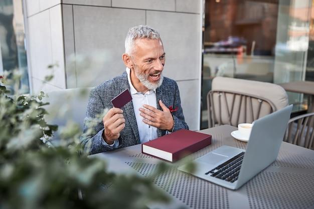 Begeisterter erwachsener mann, der bei einem videoanruf auf einem laptop eine dunkelrote plastikkarte hält und vorführt