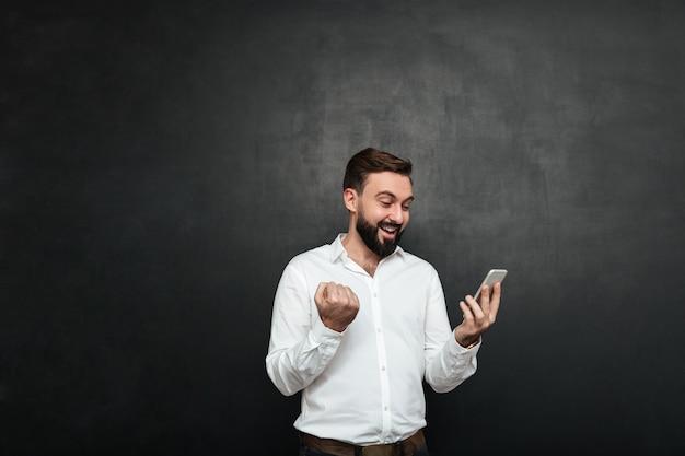 Begeisterter geschäftsmann im weißen hemd, das wie zusammenpressende faust des siegers bei der anwendung des mobiltelefons über graphit fungiert