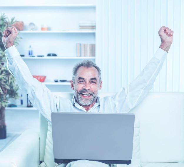 Begeisterter geschäftsmann mit offenem laptop, der im modernen büro auf dem sofa sitzt