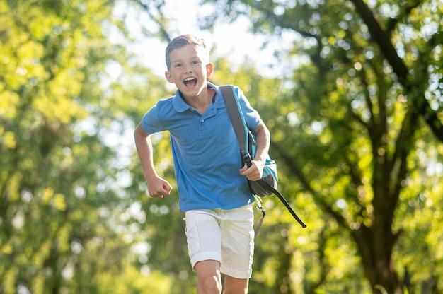 Begeisterter junge mit schultasche, der im park läuft