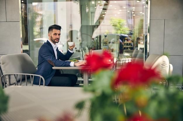 Begeisterter junger geschäftsmann, der seine kaffeepause im café genießt, während er auf seinen partner wartet