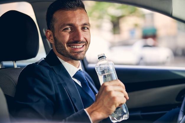 Begeisterter junger mann, der eine flasche mit wasser hält und direkt in die kamera schaut, während er auf seinem auto sitzt