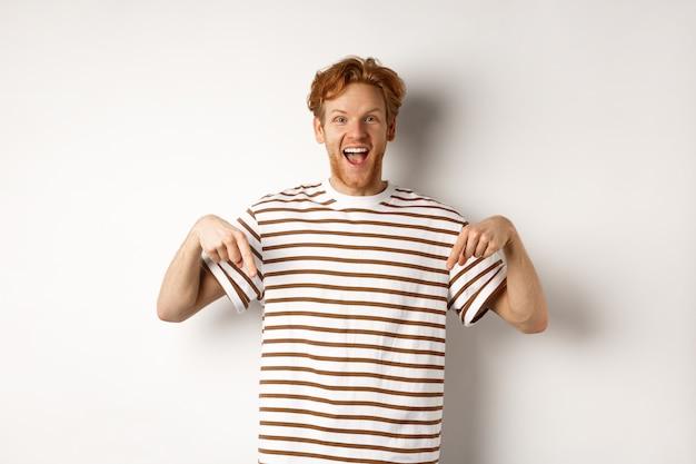 Begeisterter junger mann mit ingwerhaar und borsten, der werbung zeigt, mit den fingern nach unten zeigt und lächelt, weißer hintergrund