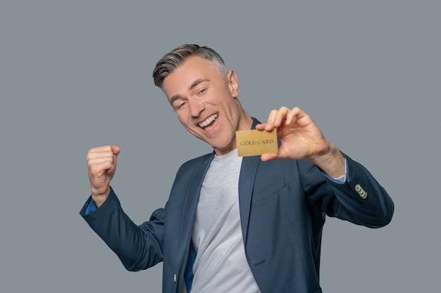 Begeisterter mann mit goldener bankkarte
