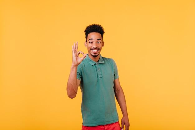 Begeisterter schwarzer kerl mit kurzen haaren, die positive gefühle ausdrücken. innenaufnahme des glückseligen afrikanischen mannes, der genießt.