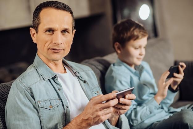 Begeisterter spieler. hübscher angenehmer mann, der neben seinem jugendlichen sohn auf dem sofa sitzt und für die kamera posiert, während er auf seinem telefon spielt, der junge, der dasselbe tut